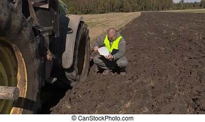 Farmer with documentation near tractor on field