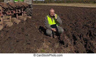 Farmer with documentation talking on smart phone near...