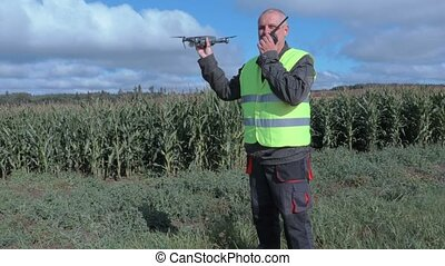 Farmer with drone and walkie talkie at corn field