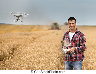 Farmer with drone in front of combine harvester