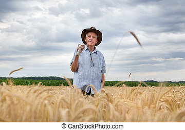 Farmer with fork in barley field