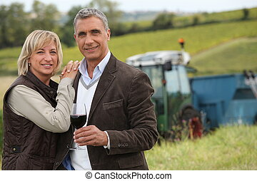 Farmer with glass of wine stood in front of tractor