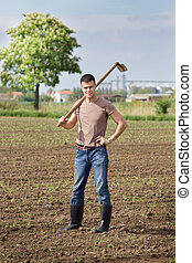 Farmer with hoe in corn field