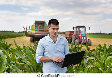 Farmer with laptop during harvest - Young attractive farmer...