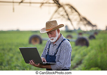 Farmer with laptop in front of irrigation system in field