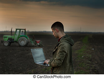 Farmer with laptop in front of tractor