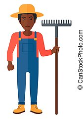 Farmer with rake. - An african-american farmer standing with...
