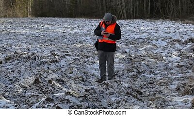 Farmer with smartphone on frozen