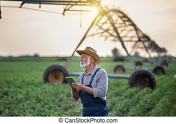 Farmer with tablet in front of irrigation system in field