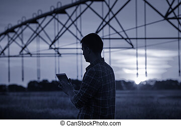 Farmer with tablet in front of irrigation system