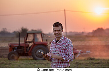 Farmer with tablet in front of tractor