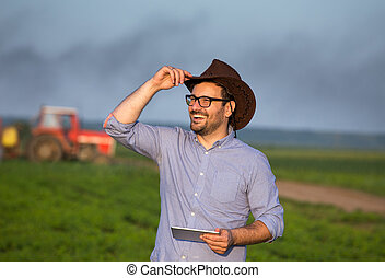 Farmer with tablet in front of tractor in field