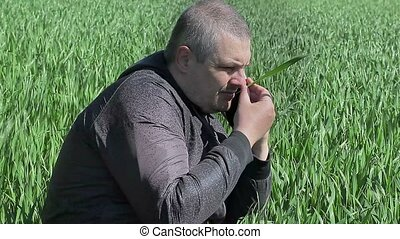 Farmer with tablet PC on green