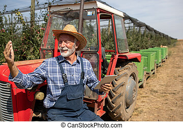 Farmer with tablet standing beside tractor in orchard
