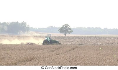 farmer with tractor prepare arable field soil with harrow...