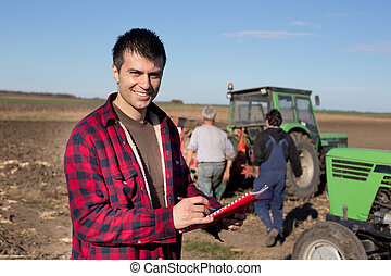 Farmer with tractors on field - Young handsome farmer...