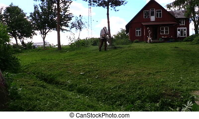 Farmer with trimmer grass - Farmer with trimmer cut grass in...