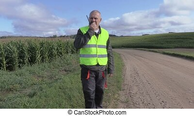 Farmer with walkie talkie on the road at the cornfield