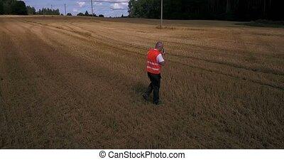 Farmer with walkie talkie walking on the field