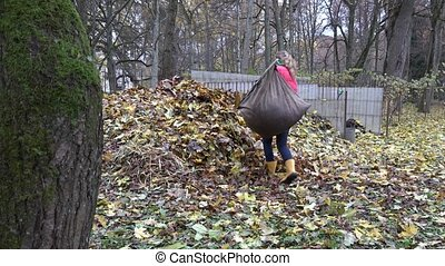 Farmer woman carry heavy sack full of leaves and dump on big...