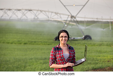Farmer woman in front of watering system
