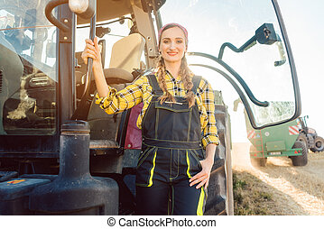 Farmer woman standing in front of tractor on wheat field