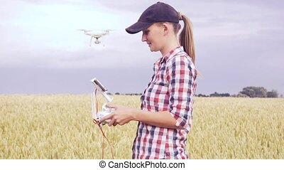 agronomist woman walking on field with drone flying above farmland at sunset