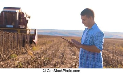 Farmer works Smart farming man read or analysis harvest lifestyle sunflower a report in tablet computer on a agriculture field with vintage tone on a sunlight. the combine harvester plows a field agriculture concept. Concept ecology farmer tablet