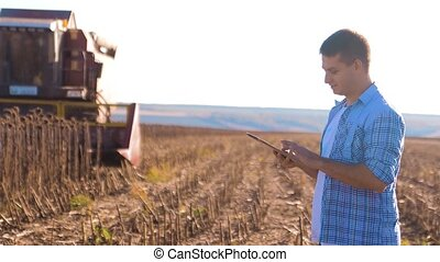 Farmer works Smart farming man read or analysis harvest sunflower a report in tablet computer on a agriculture field with vintage tone on a sunlight. the combine harvester plows a field agriculture concept. Concept ecology farmer lifestyle