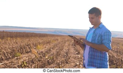 Farmer works Smart farming man read or analysis harvest sunflower a report in tablet computer on a agriculture field with vintage tone on a sunlight. the combine harvester plows a field lifestyle agriculture concept . Concept ecology farmer