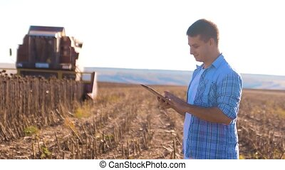 Farmer works Smart farming man read or analysis harvest sunflower lifestyle a report in tablet computer on a agriculture field with vintage tone on a sunlight. the combine harvester plows a field agriculture concept. Concept ecology farmer tablet