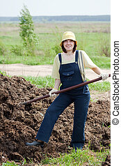 farmer works with manure at field - Female farmer works with...