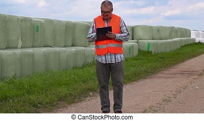 Farmer writing and walking near hay bales