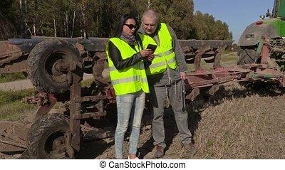 Farmers couple talking near tractor on field