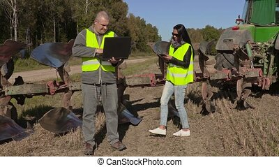 Farmers couple with computer and tablet near plow