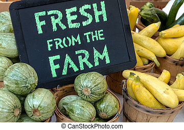 Fresh from the Farm sign on table full of vegetables in baskets on display at local farmers market