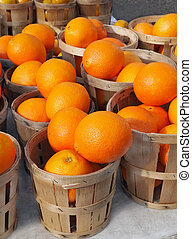 Baskets full of beautiful oranges for sale at the farmer's market on a bright, sunny morning.