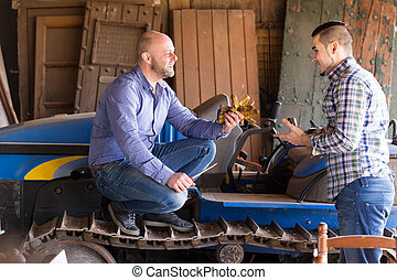 Farmers near agricultural machinery - Two farmers talking...