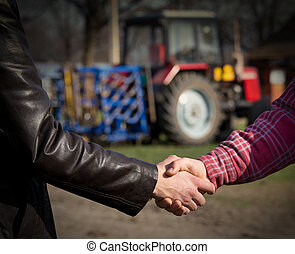 Farmers shaking hands - Two farmers shaking hands in front...