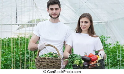 Farmers with a basket full harvest smiling directly at the camera