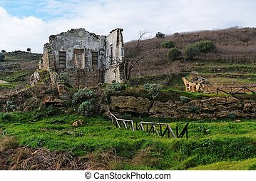 Farmhouse ruin among rural landscape