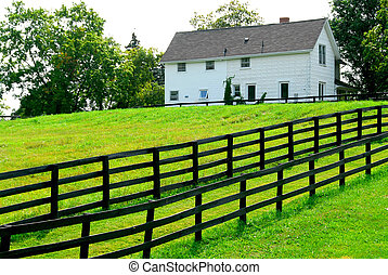 Farmhouse with fence among green fields