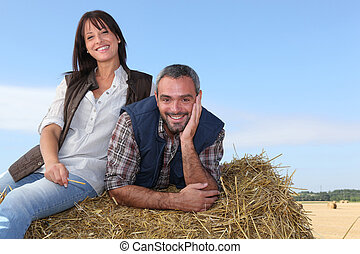 Farming couple sitting on a haystack