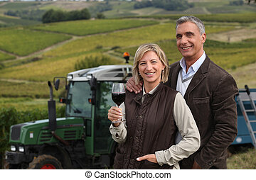Farming couple stood in field in front of tractor