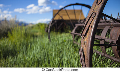 Farming ranch background with barn and rusty farm plow. Green grass, blue sky and wooden barn. Shallow depth of field with focus on rusty plow wheel.