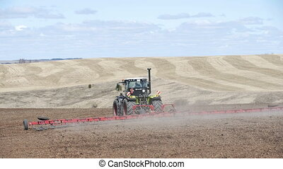 Farming tractor moving on agricultural field for plowing...