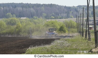 Farming tractor moving on agricultural field for sowing...
