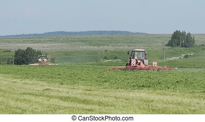 Farming tractors moving on agricultural field for harvesting...