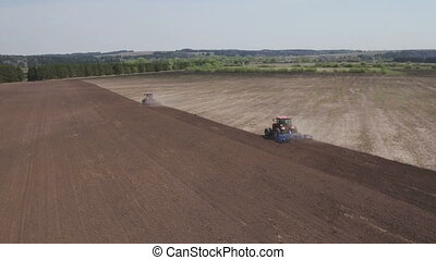 Farming tractors moving on agricultural field for plowing...