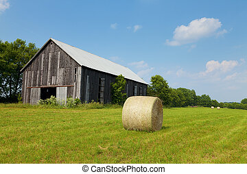 Hay bales in a field with an old barn on a sunny day